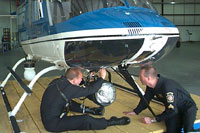 Photograph of Aviaion Pilots working On Helicopter